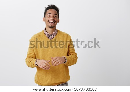 Funny friend tells hilarious jokes. Indoor shot of pleased happy african-american in stylish outfit smiling broadly and gesturing over chest during conversation, having nice talk with coworker