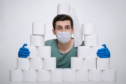 Funny frightened man in face mask and medical gloves hoarding toilet paper and hiding behind it to prevent Coronavirus outbreak. White background. COVID-19 pandemic concept. Home isolation, panic.