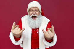Funny funky happy crazy old bearded hipster Santa Claus wearing hat, glasses, costume looking at camera showing horns hand gesture celebrating Merry Christmas, isolated standing on red background.