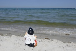 Funny garden gnome, a football fan with number 10 on the back of his jersey. He is sitting at the beach  makes holidays  at the sea.