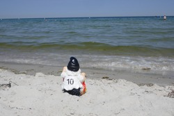 Funny garden gnome, a football fan with number 10 on the back of his jersey. He is sitting at the beach  makes holidays  at the sea