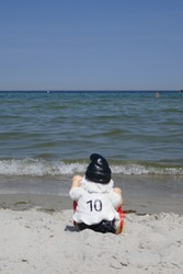 Funny garden gnome, a football fan with number 10 on the back of his t-shirt. He is sitting at the beach  makes holidays  at the sea
