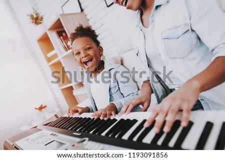 Funny Girl amd Happy Mother Play on Piano Together. Hobbies For Mother and Young Daughter. Happy Mother with Little Girl Play on Piano. Positive Day for Beautiful Woman. Young Daughter.