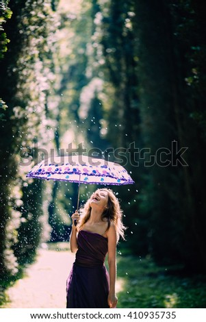 funny girl catching rain on a sunny day and feel joy