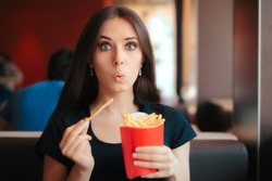 Funny Girl Eating Fries in French Fast Food Restaurant. Hungry woman having a quick unhealthy snack at a dinner