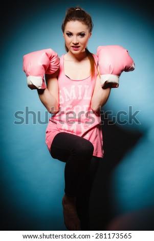 Funny girl female boxer model wearing big fun pink gloves playing sports boxing studio shot blue background