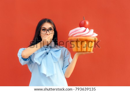 Funny Girl Holding Big Huge Giant Sweet Muffin Cupcake. Woman with a sweet tooth considering to eat huge patty cake
