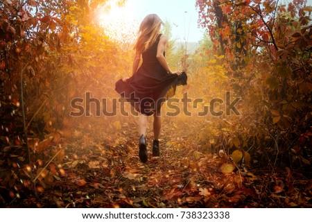funny girl in black dress running in golden autum forest