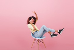Funny girl in black sneakers and white socks posing in studio with pink interior and listening favorite song. Indoor photo of charming african woman in trendy jeans sitting on chair.