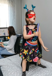 Funny girl in disguise singing and dancing on the bed while her mother works from home. Conciliation family work concept