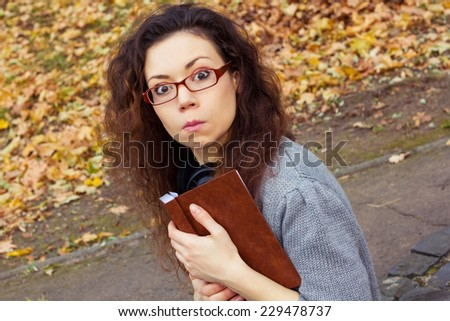 Funny girl in glasses with a book in the park. Girl grimaces. Girl with the book in autumn park