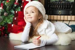 Funny girl in Santa hat writes letter to Santa near christmas tree