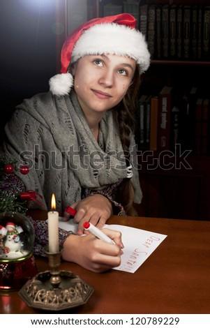 Funny girl in Santa hat writes letter to Santa near cristmas tree