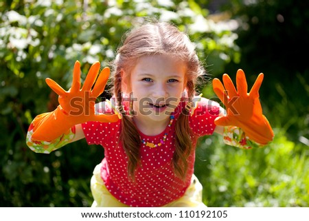 Funny girl in the orange garden gloves
