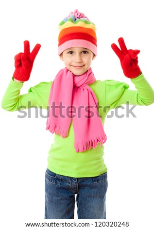 Funny girl in winter clothes with victory sign, isolated on white