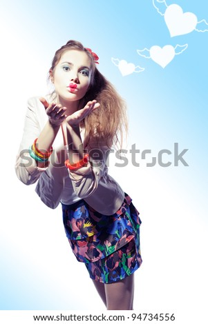 Funny girl is sending a kiss, her lips are heart shaped. Three graphic hearts on the wings are flying away. - stock photo