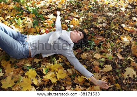 funny girl lying on the yellow leaves  in the autumn forest