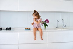 Funny girl on kitchen in dress having fun. Cute toddler is sitting on white furniture and eating cookies.