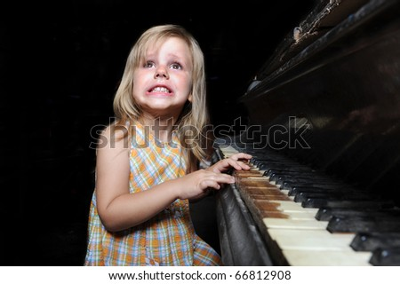 Funny girl playing on an old black piano - stock photo