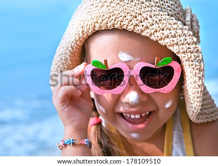Funny girl wearing sunscreen on your face