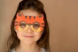 funny girl with beautiful blue-orange eyes in a cardboard mask in the form of a tiger plays at home. close portrait.