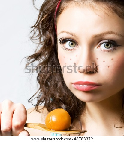 Funny girl with big eyes wanting to eat this stewed apricot (Close-up funny face)