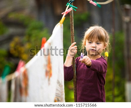 Funny girl with clothespin and the clothesline - stock photo