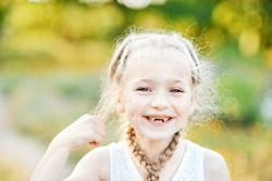 Funny girl with hair plaits. Kid expressing emotions. Close up portrait of beautiful joyful blonde Caucasian girl smiling demonstrating white teeth without two front teeth. Cheerful child.
