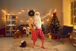 Funny grandpa having fun at Christmas or New Year disco night party at home. Old Santa Claus in polka dot underwear and red and white striped socks holding present and dancing in decorated living-room