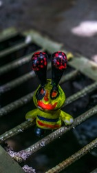 Funny green alien doll toy on the sewer portrait