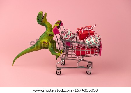 funny green dinosaur toy with shopping cart full of present boxes on a soft pink background