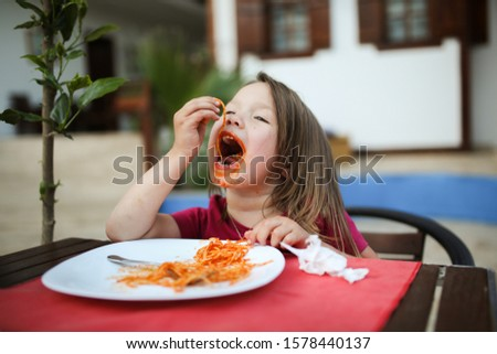 Funny grimy girl child eating pasta with tomato sauce in a cafe on the street, poor behavior at the table, ill-bred dirty child. Children's crisis and protest Stock fotó ©