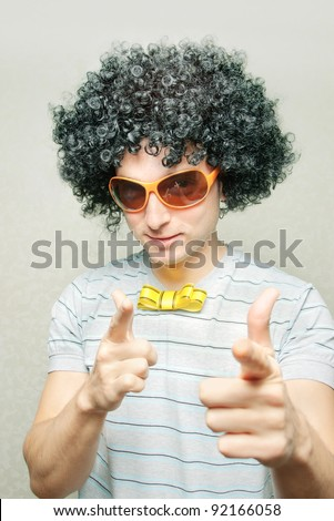 funny guy in afro curly wig with eyeglasses and ribbon bowtie pointing with his fingers - stock photo