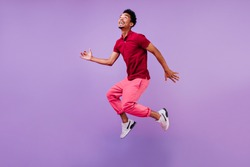 Funny guy in red t-shirt jumping and looking up. Studio portrait of emotional african male model posing on purple background.