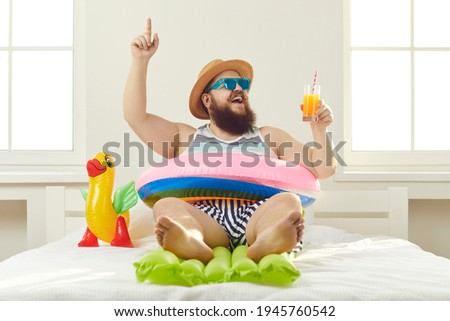 Funny guy in sunglasses, sun hat and swim ring sitting on beach mattress and sipping cocktail points finger up struck by cool idea on how to turn quarantine holiday at home into fun summer vacation