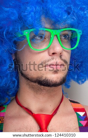 Funny guy naked with blue wig and red tie on green background