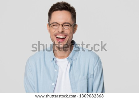 Funny guy nerd wearing glasses laughing at humorous hilarious silly joke looking at camera isolated on white grey blank background, happy cheerful young man chuckling giggling having fun portrait