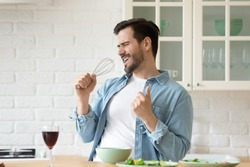 Funny guy singing song holding beater whisk microphone listening music in modern kitchen, happy joyful young man having fun cooking dancing preparing healthy dinner meal drink wine alone at home
