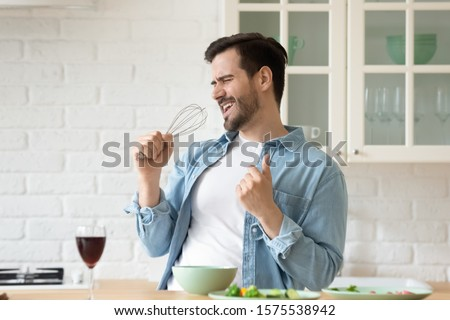 Photo of Funny guy singing song holding beater whisk microphone listening music in modern kitchen, happy joyful young man having fun cooking dancing preparing healthy dinner meal drink wine alone at home