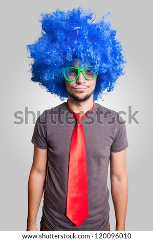 funny guy with blue wig green eyeglasses and red tie on grey background