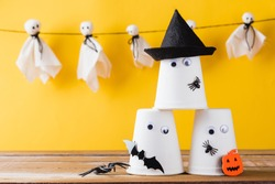 Funny Halloween day decoration party, Baby cute white ghost crafts scary face hanging and halloween crafts paper cup ghost on wood, studio shot isolated, Happy holiday DIY handicraft concept