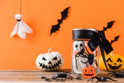 Funny Halloween day decoration party, Baby white ghost crafts scary face in jar glass and cute pumpkin ghost on wood table, studio shot isolated on orange background have spider and bats