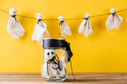 Funny Halloween day decoration party, Cute white ghost crafts scary face hanging on background have only one baby ghost in jar glass, isolated yellow, Happy holiday DIY handicraft concept
