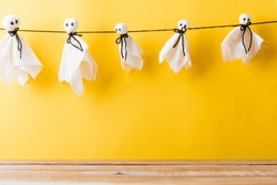 Funny Halloween day decoration party, Full body of baby cute white ghost crafts scary face hanging and wooden space, studio shot isolated on yellow background, Happy holiday DIY handicraft concept