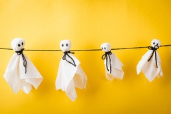 Funny Halloween day decoration party, Full body of baby cute white ghost crafts scary face hanging, studio shot isolated on yellow background, Happy holiday DIY handicraft concept