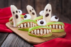 Funny halloween eadible monsters scary food healthy vegetarian snack dessert recipe for party decoration. Homemade spooky cyclop apples with teeth and banana ghosts on vintage wooden background
