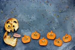Funny Halloween food background bread monster eats small pumpkin