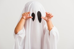 Funny Halloween Kid Concept, little cute child with white dressed costume halloween ghost scary, studio shot isolated on white background
