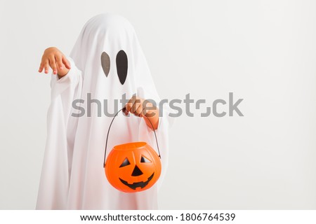Funny Halloween Kid Concept, little cute child with white dressed costume halloween ghost scary he holding orange pumpkin ghost on hand, studio shot isolated on white background