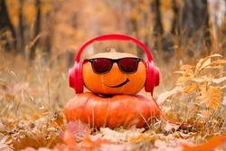 Funny Halloween. Pumpkin in sunglasses in the autumn Park